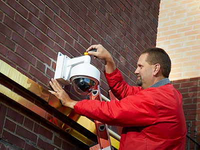 Sonitrol agent installing security device on ladder