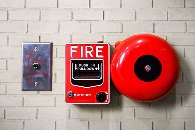 Red fire alarm on white brick wall